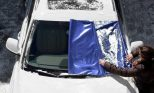 winter-windshield-cover being removed from car windshield